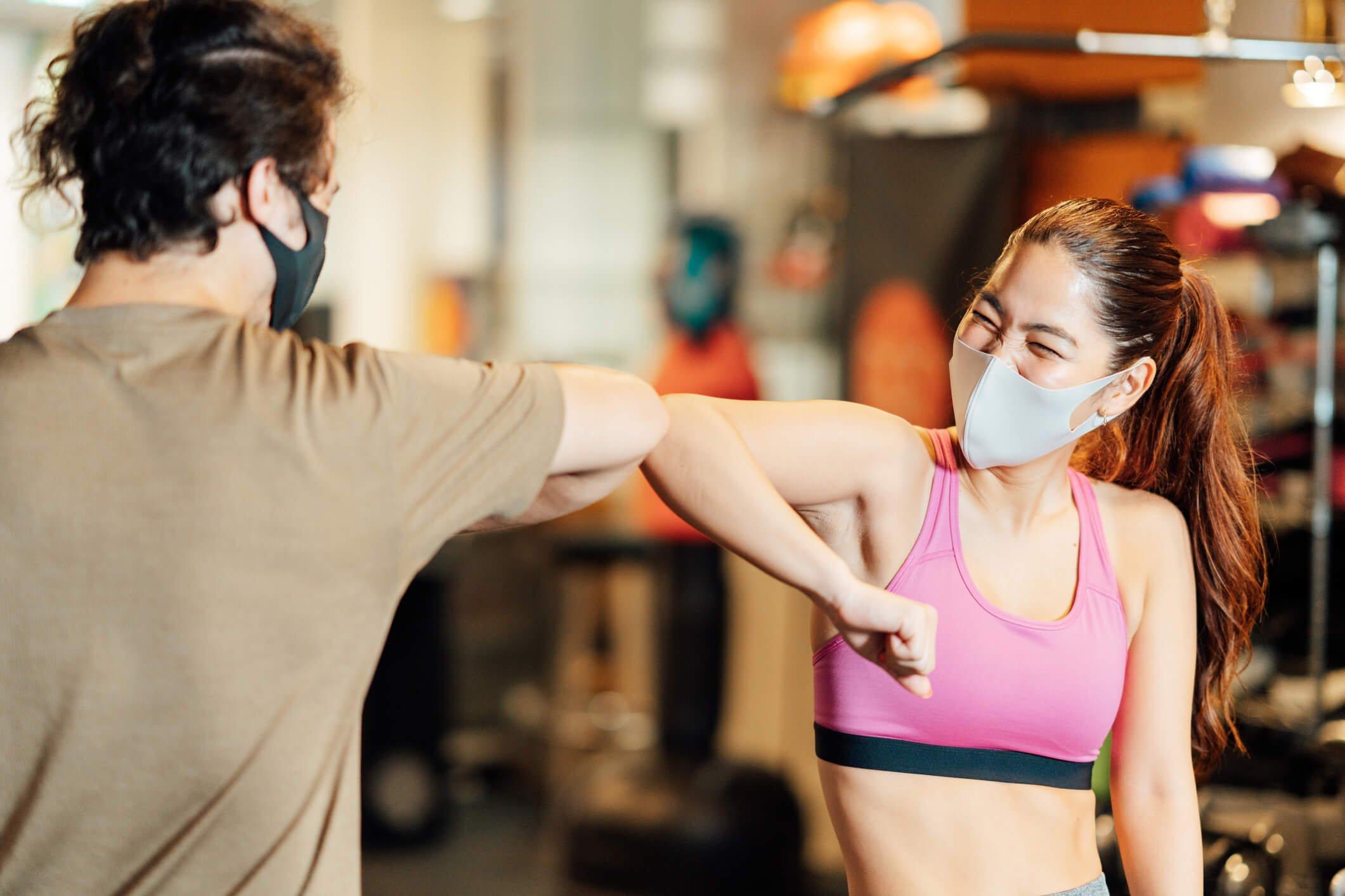 2 athletes elbow bumping good job at gym in masks