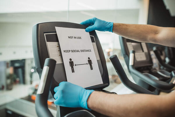 Affixing social distance sign to treadmill with gloves