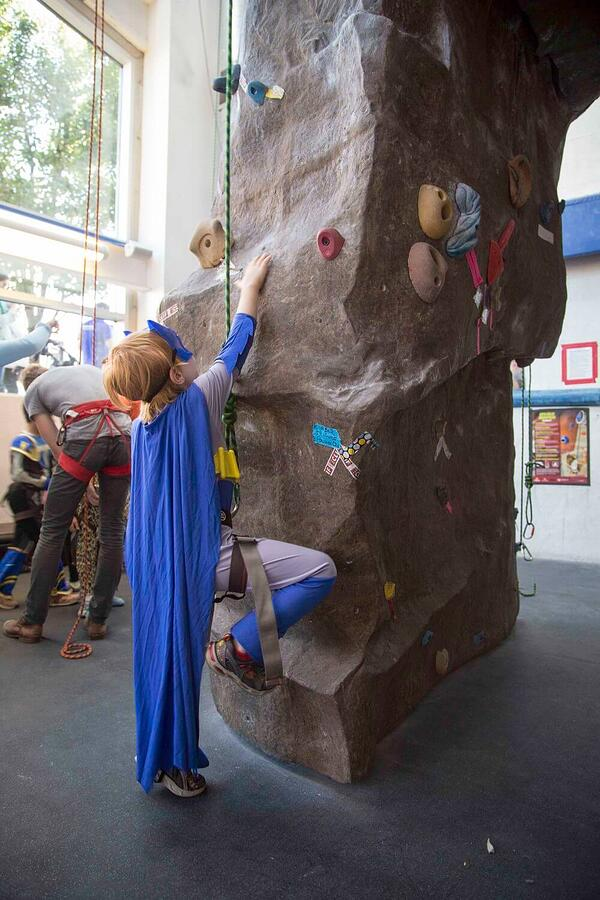 Child in costume perparing to climb LVAC Climbing Wall.