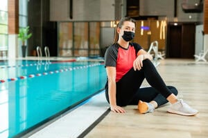 Girl in workout clothes and mask sitting by the pool