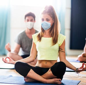 Woman doing yoga with facemask